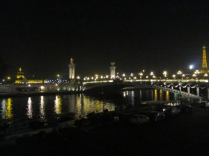 The Eiffel Tower, Pont Alexandre III and Hôtel des Invalides at night.
