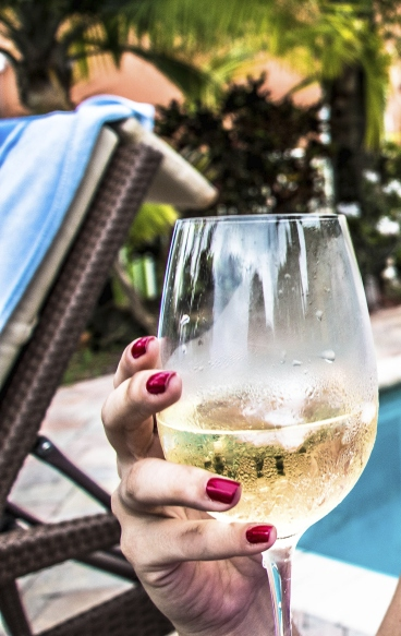 Lady holding white wine by pool.jpg