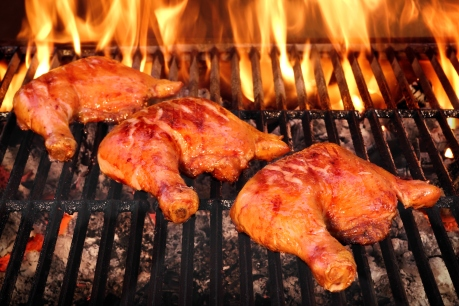 Three Crispy And Tasty BBQ Chicken Quarters Roasted On The Hot Charcoal Flaming Grill, Closeup, Top View
