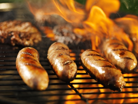 bratwursts cooking over fire on barbecue grill with hamburgers in background with flames.